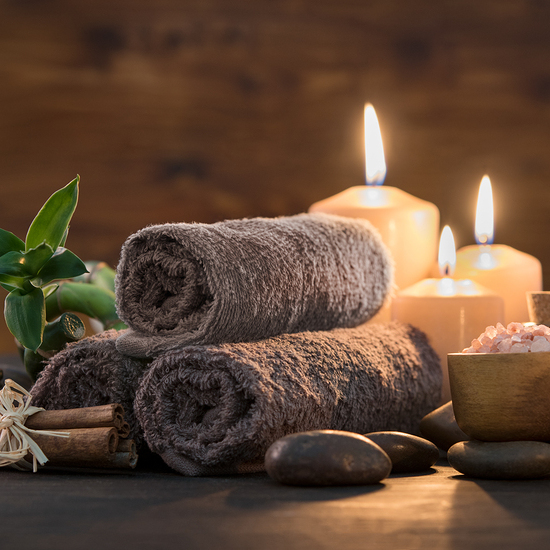 Brown towels with bamboo and candles for relax spa massage and body treatment. Composition with candles, spa stones and salt on wooden background. Spa and wellness setting ready for beauty treatment.